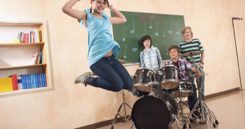 Students at music class girl jumping smiling  boy playing drums classmates standing behind