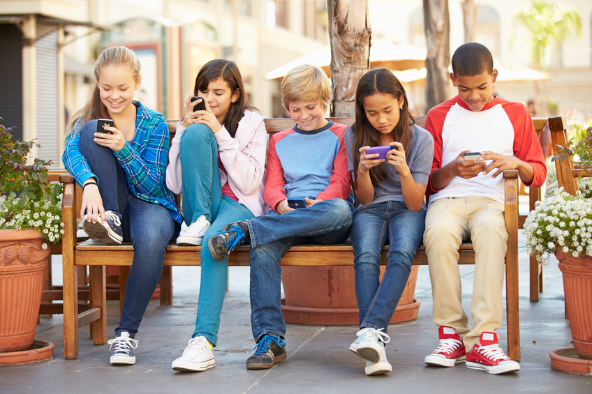 Group Of Children Sitting In Mall Using Mobile Phones Smiling